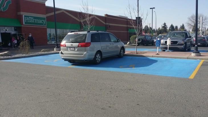 Camioneta estacionada en medio de dos lugares para discapacitados en un estacionamiento