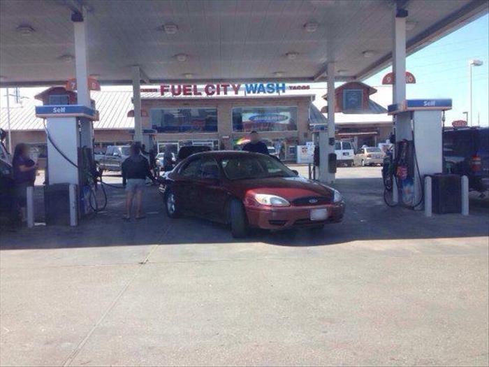 Mujer despachándose gasolina un poco lejos de la bomba de gasolina