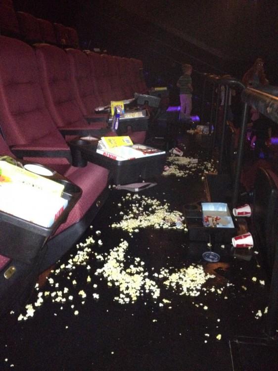 Sala de cine con muchas palomitas tiradas en el suelo