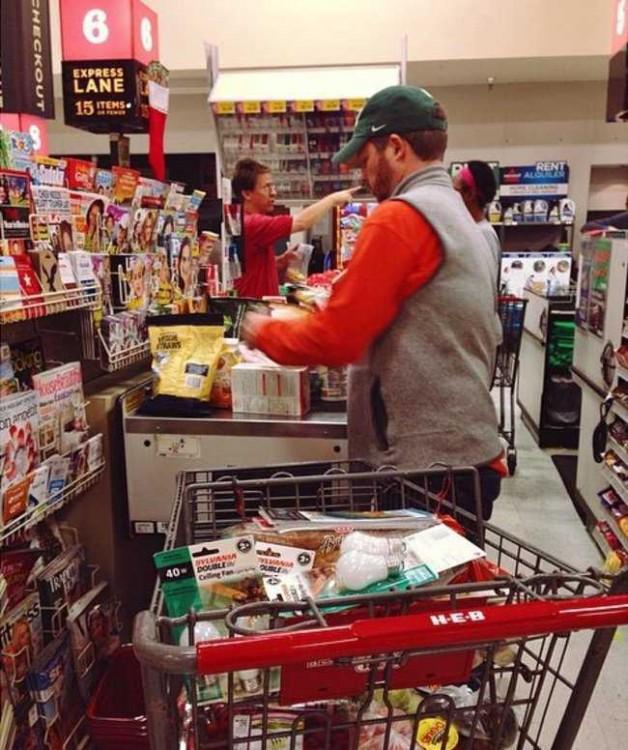 Un hombre con un carro de supermercado lleno de muchas cosas en la fila de una caja rápida
