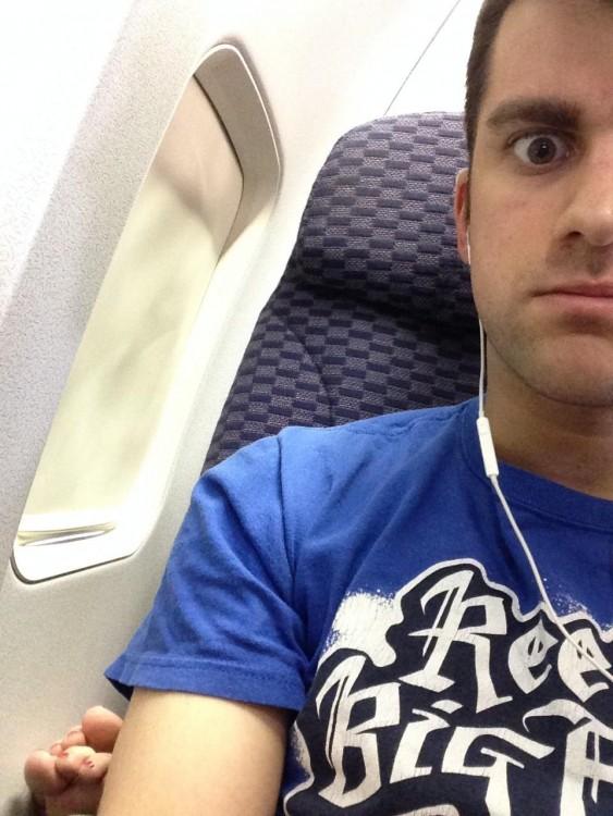 Selfie de un chico en una avión con el pie de una persona a un lado