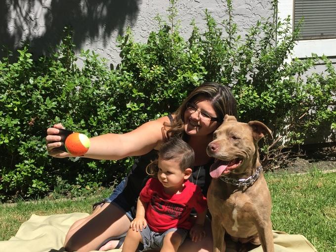 Mujer tomándose una selfie con su perro y su bebé