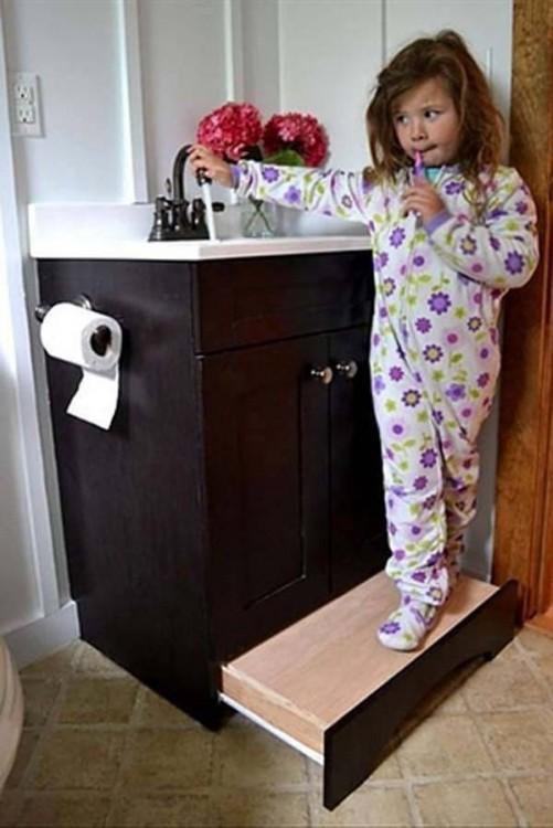 Niña sobre un escalón corredizo en el gabinete de baño