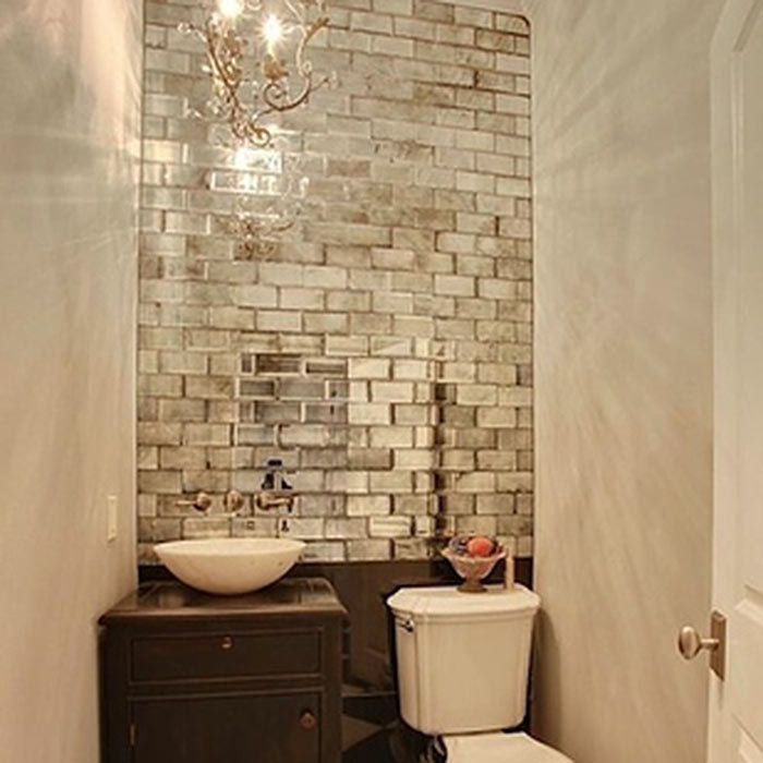 Pared de un baño con azulejos que reflejan luz