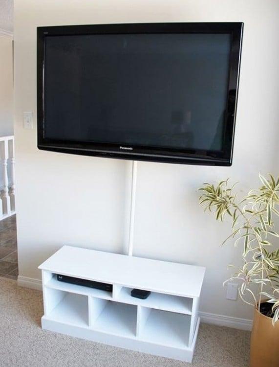 Mueble blanco con un tubo sosteniendo una televisión cerca de una pared