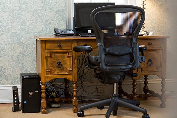 Escritorio con artículos de oficina y módem en el suelo