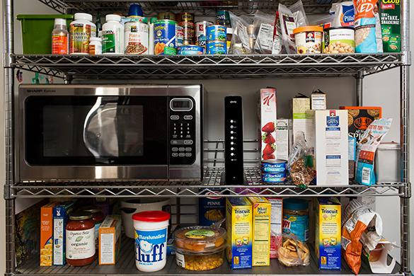 Mueble con algunos productos de comida y un módem a lado de un microondas