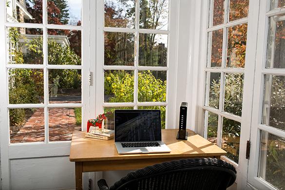 Escritorio con una computadora y un módem cerca de una ventana