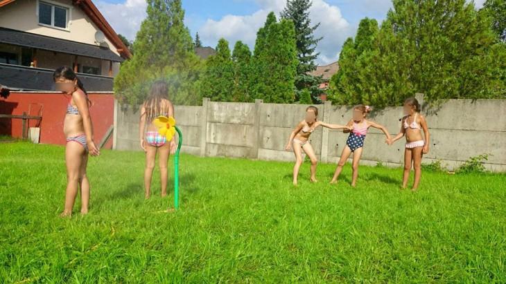 niñas jugando a mojarse en su jardín