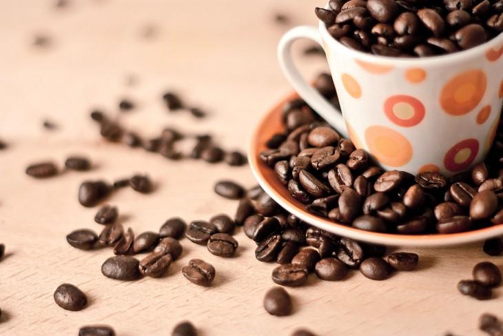 granos de café en una taza con puntos naranjas