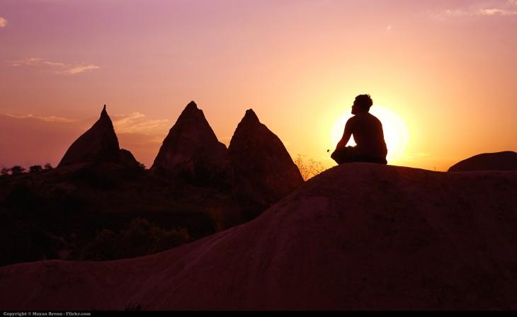 hombre meditando en la cima