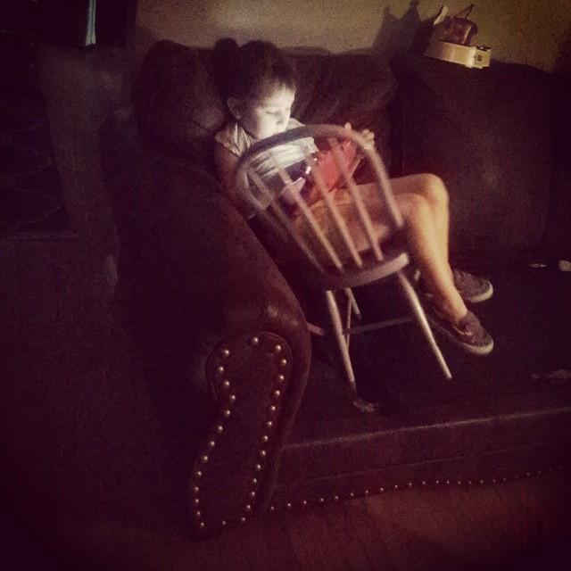 niña utilizando la silla arrriba de un sillon