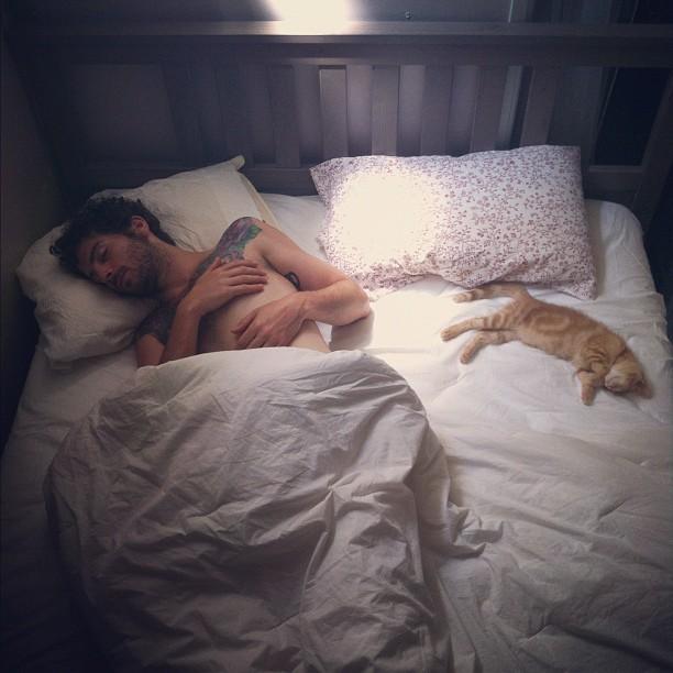 hombre dormido con su gato en un rincón de la cama