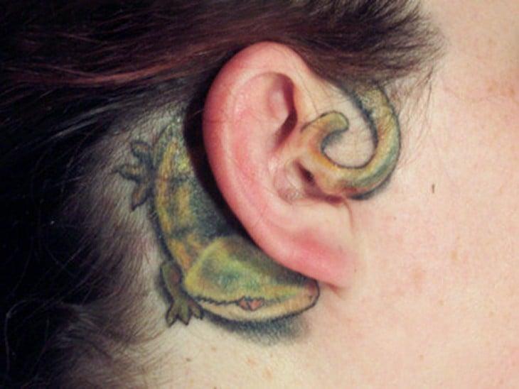 tatuaje de una iguana en la oreja