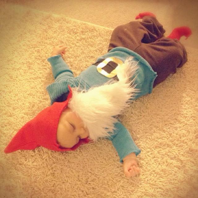 bebé disfrazado de papa pitufo recostado en una alfombra
