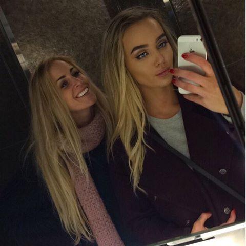 hermanas tomandose una selfie frente al espejo ambas con un iphone