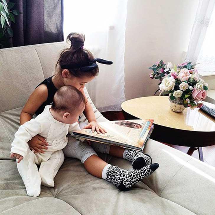 hermana enseñandole a leer a su hermanito