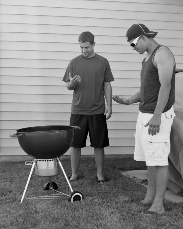amigos haciendo carne asada mientras ven el telefono