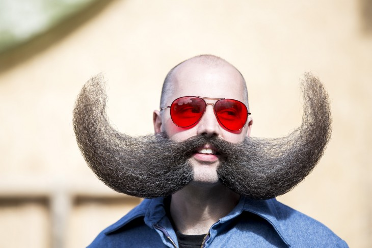 Cara de un hombre con lentes rojos y un bigote de gran tamaño