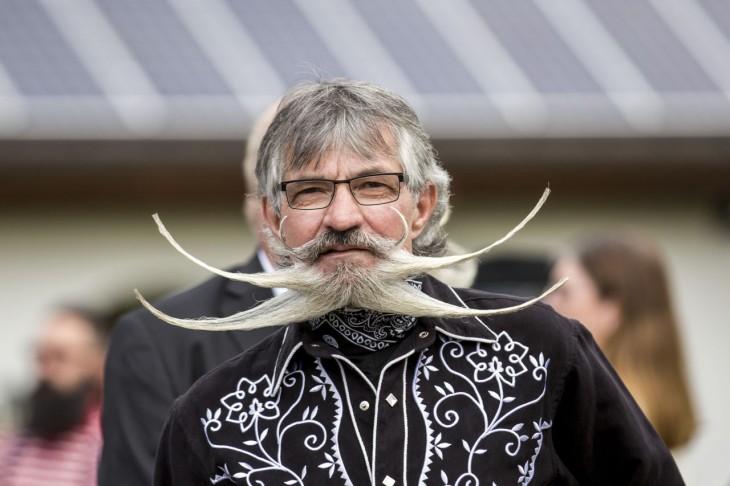 hombre de negro con una barba y bigote demasiado largo acomodado a los costados