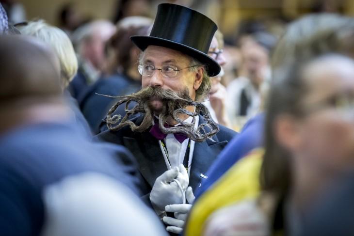 fotografía de un hombre con barba y bigote largo en medio de muchas personas