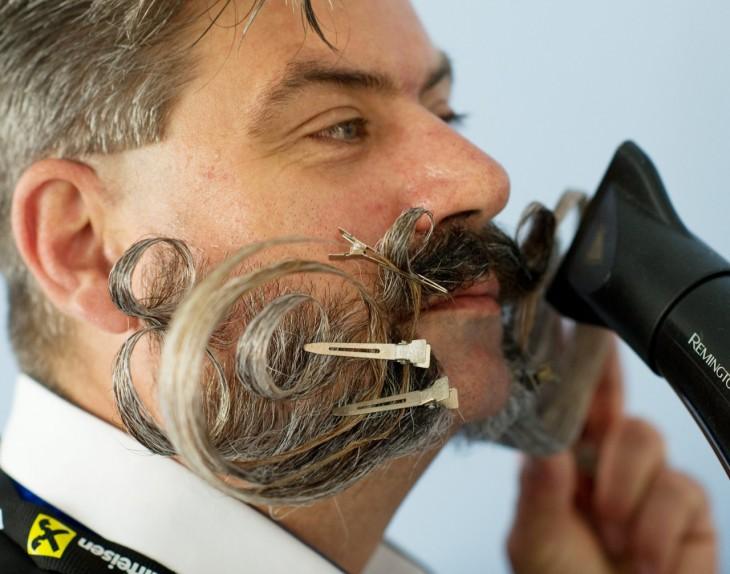 Cara de un hombre con una gran barba y bigote peinandose con una secadora de cabello