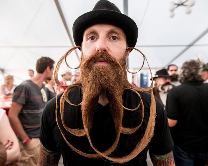 fotografía de un chico con una barba y bigote demasiado largo y un increíble diseño hecho con ella