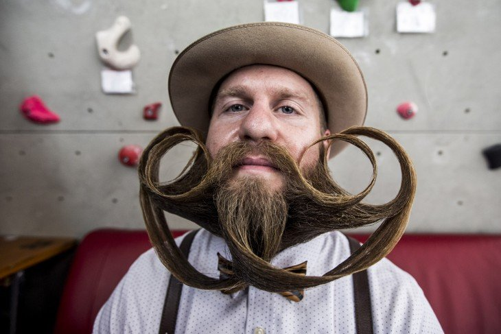 Chico con un sombrero y una barba y bigote peinado en el Campeonato Mundial de Barba y Bigote