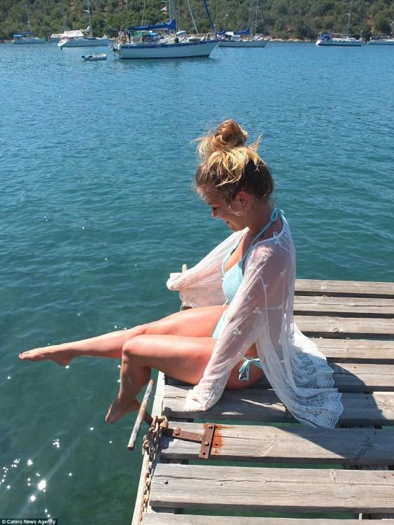 Chica sentada a la orilla de un puente mojando sus pies en el agua
