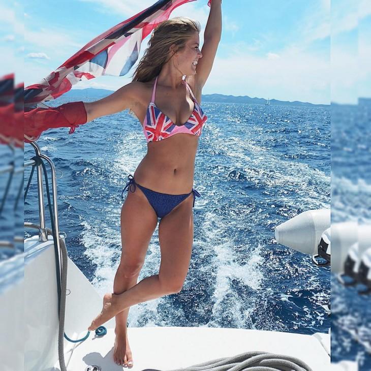 Una chica en bikini sobre un barco con una bandera de londres