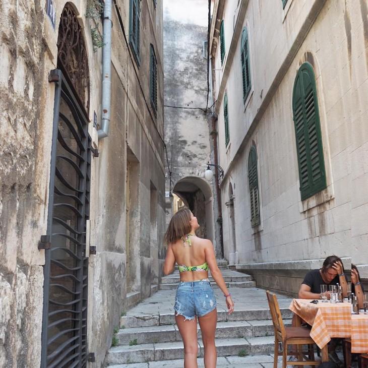 Espalda de una chica que va caminando por una calle