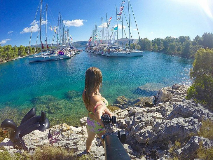 Selfie de una chica frente a unos barcos a la orilla de un rió