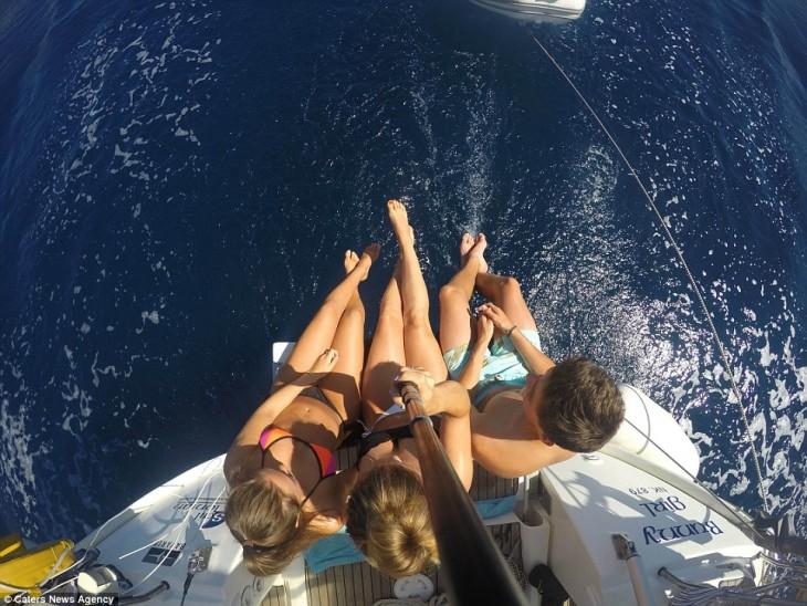 selfie de tres chicas sentados a la orilla de un bote viendo hacia el mar