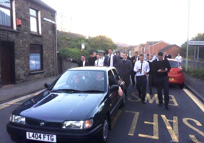 chicos caminando detrás de un coche fúnebre