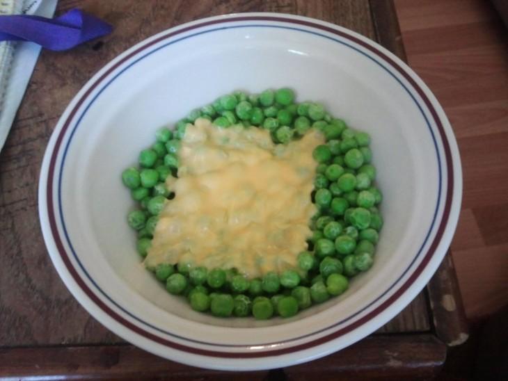 Platillo lleno de chicharos verdes con una rebanadita de queso