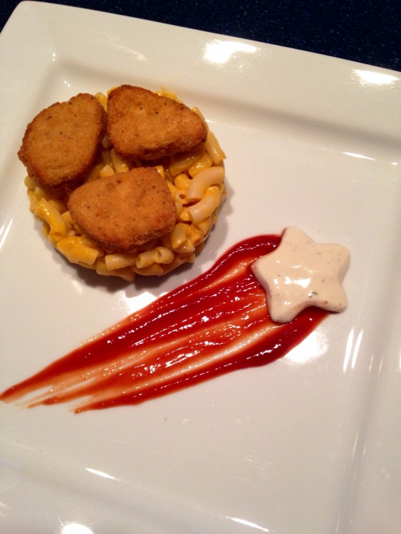 Nuggets de pollo sobre sopa de macarrones junto a una estrella de queso con catsup