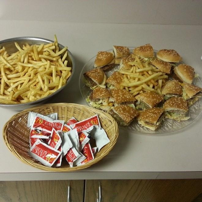 tres recipientes uno con papas fritas, otro con pedazos de hamburguesas y otro con sobres de catsup