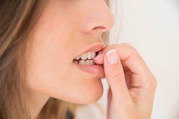 cara de una chica con las uñas en la boca