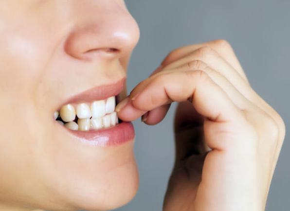 boca de una chica mordiéndose las uñas de las manos