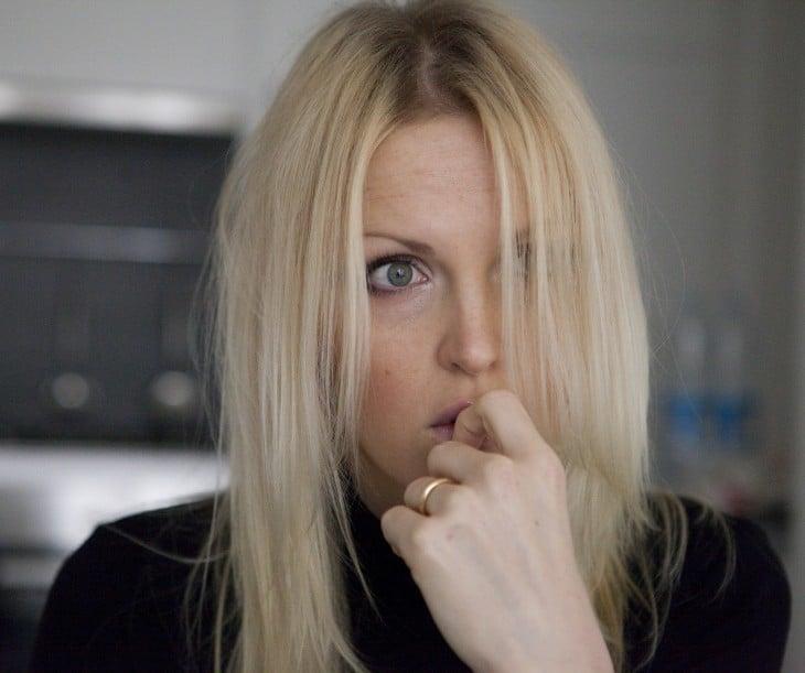 cara de una mujer ansiosa con la mano en la boca