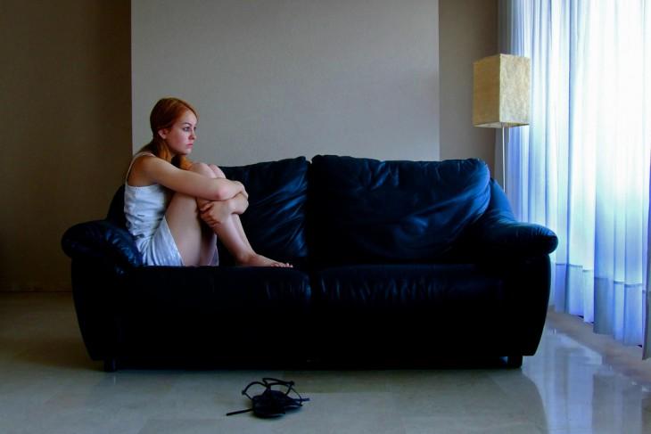 chica sentada con los pies doblados en un sillón viendo hacia una ventana