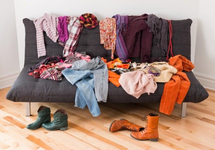 sillón con ropa de muchos colores desordenada