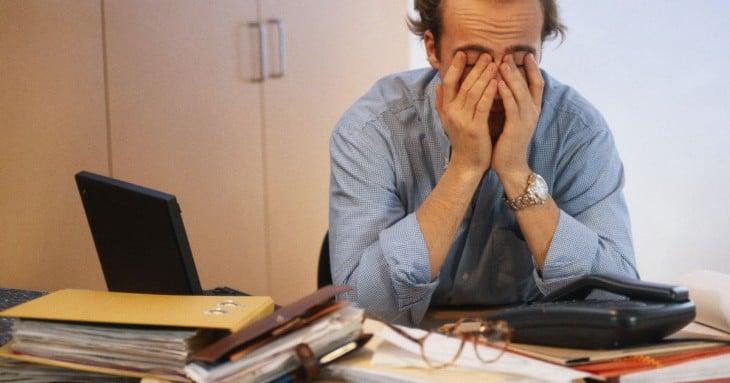 homem em um escritório com as mãos sobre os olhos