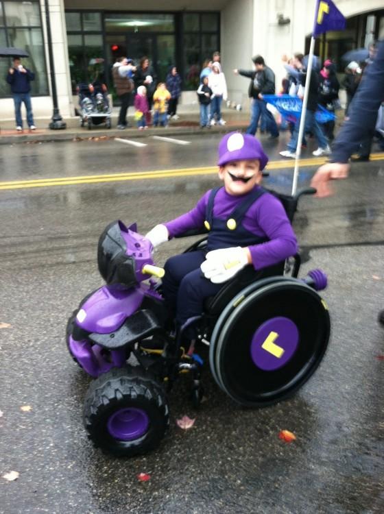 Niño con un disfraz de Waluigi de Mario Kart en su silla de ruedas