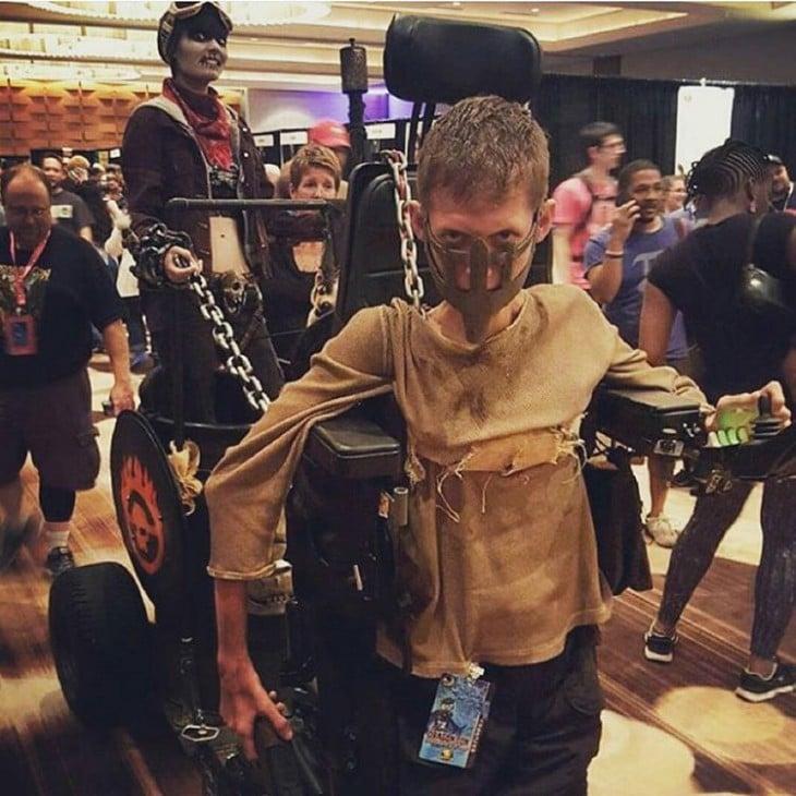 Niño con discapacidad disfrazado de Nux Bloodbag Chariot, Md Max: Fury Road