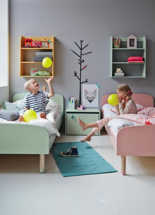 dos niños en una habitación con dos camas lleno de juguetes