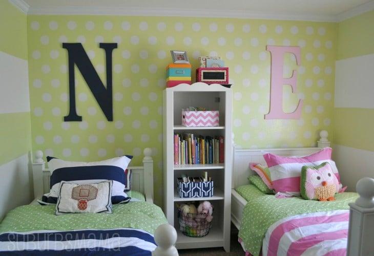 habitación con dos camas divididas por un mueble y con las iniciales N y E