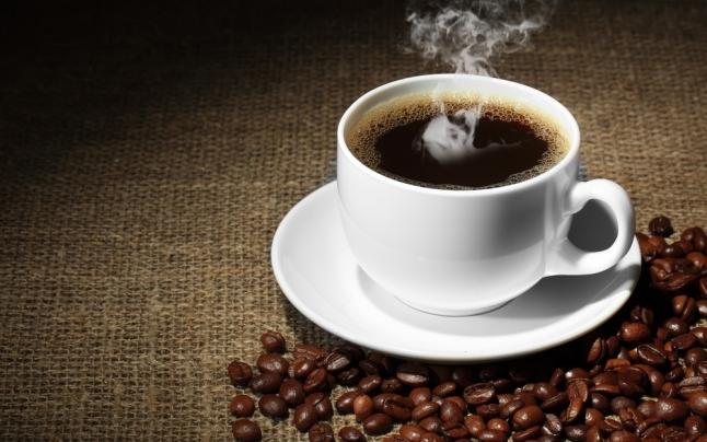 Taza de café cerca de un montón de granos de café puro