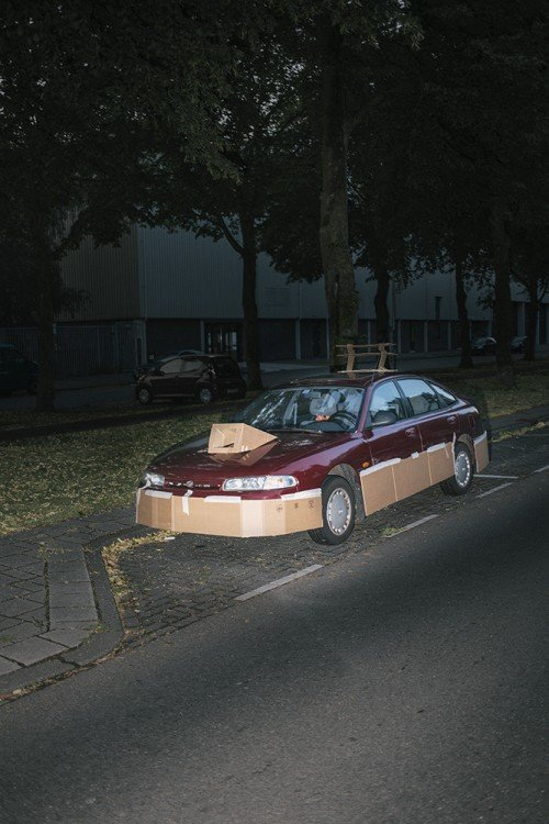 Carros en color rojo estacionado en una calle con unas piezas de cartón