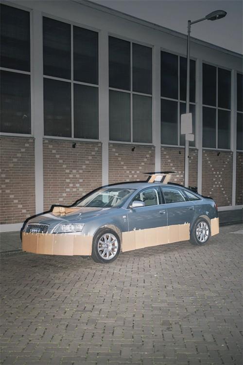 carro gris parado afuera de una casa con cartón y cinta adhesiva